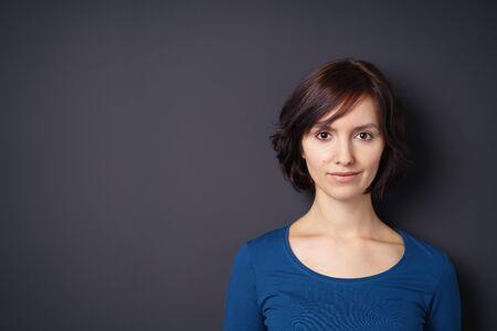 mujer sola: Cierre de la mujer atractiva joven delgado que mira la cámara con la media sonrisa de la cara contra la pared gris con espacio de copia. Foto de archivo