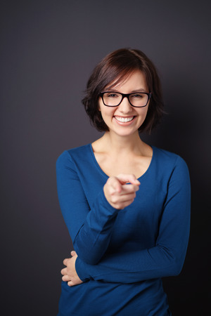 mirth: Half Body shot of a Happy Young Woman with Eyeglasses, Pointing at You Against Gray Wall Background.