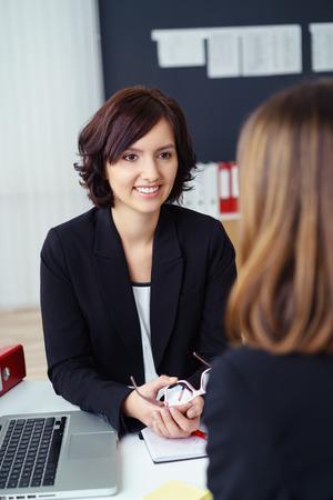 personas escuchando: Empresaria joven sonriente que habla con su compañero de trabajo femenino en su escritorio dentro de la oficina.