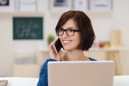 attractive office: Happy Young Woman with Laptop Talking to Someone Through Mobile Phone at the Living Room While Looking Away.