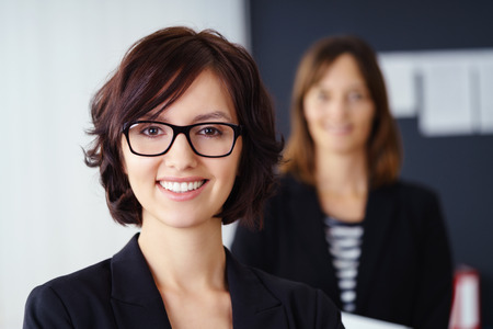 authority: Smiling attractive manageress or team leader posing in the foreground with a team member or co-worker visible in the background as a blur, head and shoulders portrait