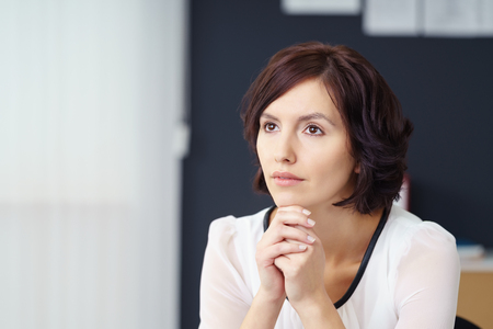 chin on hands: Close up Pensive Professional Woman Looking Away, with her Chin Resting on her Hands, Inside the Office. Stock Photo