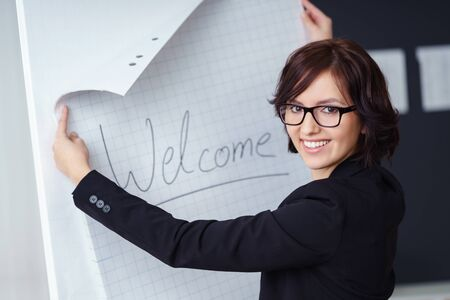 pinning: Attractive businesswoman wearing glasses preparing to start a presentation pinning up a sheet of paper saying Welcome on a board turning to smile at the camera