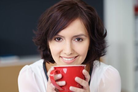energising: Close up Attractive Young Office Woman Holding a Red Cup of Hot Drink Using Two Hands and Smiling at the Camera Stock Photo