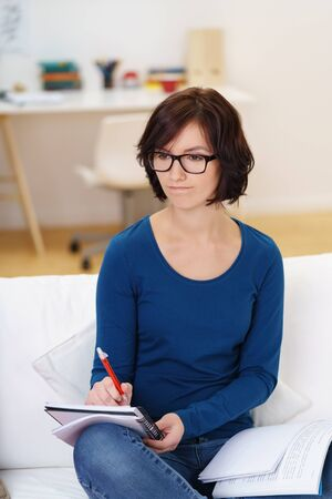 seeking an answer: Thoughtful Woman Sitting at the Living Room Couch and Looking Away While Thinking What to Write on her Notes. Stock Photo