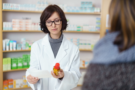 scripts: Female Pharmacist Reading the Medical Prescription While Holding a Bottled Medicine in front of the Customer at the Pharmacy Counter.