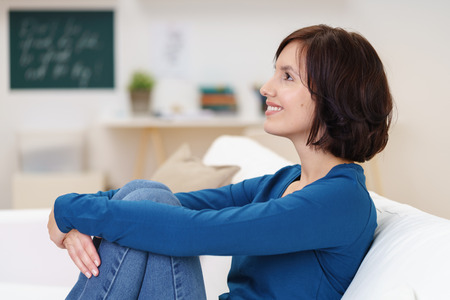 hugging knees: Side View of a Happy Thoughtful Young Woman Sitting on Couch and Embracing her Legs.
