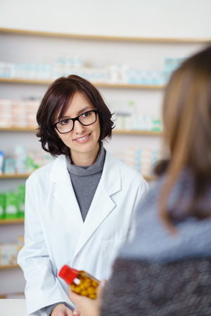 half body: Half Body Shot of an Approachable Female Pharmacist Talking to a Customer in Buying Correct Drugs.