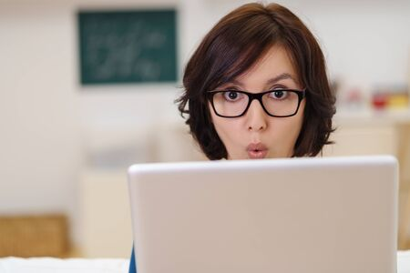delighted: Young Businesswoman with Laptop Computer Looking at the Camera with Surprised Facial Expression.
