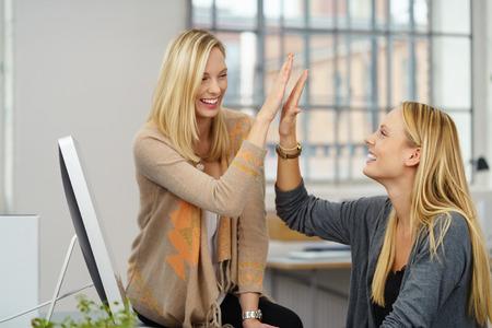 jovenes empresarios: Dos jóvenes empresarios acertados del hombre sentado a la mesa, dando de alta cinco gesto con las caras felices.