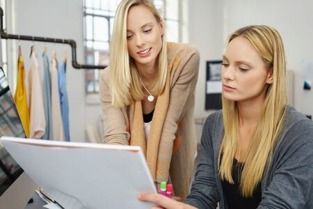 proposed: Two Young Female Fashion Designers Discussing the Proposed Style Sketched on a Paper at the Office.