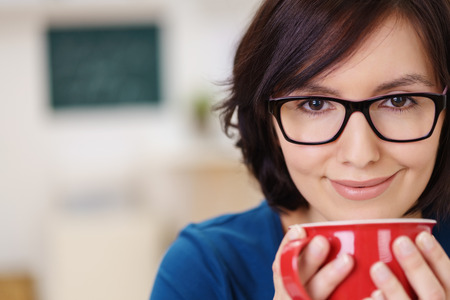 energising: Close up Smiling Pretty Woman with Eyeglasses Holding a Red Cup of Coffee in the Office. Stock Photo