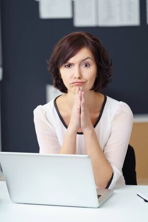 quizzical: Young Office Woman Sitting at her Desk with Laptop, Looking at the Camera with Confused Facial Expression. Stock Photo