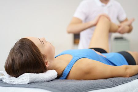 leg injury: Injured Young Woman Lying on a Therapy Bed While her Personal Physical Therapist is Massaging her Leg. Stock Photo