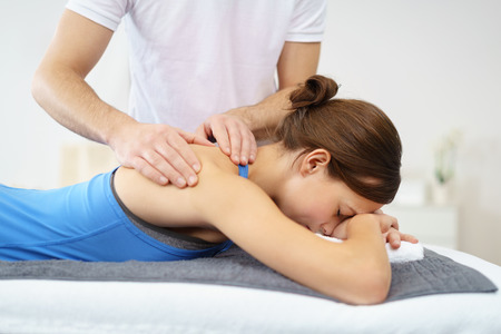 manipulating: Half Body Shot of a Young Woman, Lying in Prone Position, Having a Massage on her Injured Shoulder.