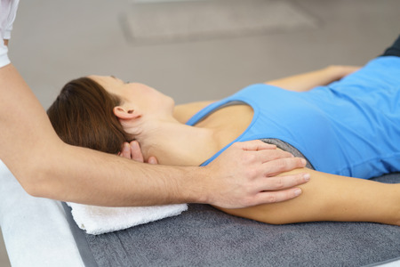 aligning: Professional Physical Therapist Stretching the Injured Neck of a Female Patient Lying on Bed.