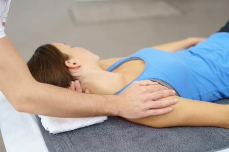 collo: Professionale Fisioterapista stretching i feriti collo di una paziente disteso sul letto.