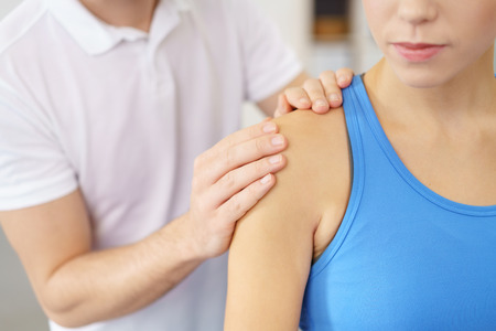 hand on shoulder: Close up Professional Physical Therapist Massaging the Injured Shoulder of a Female Patient