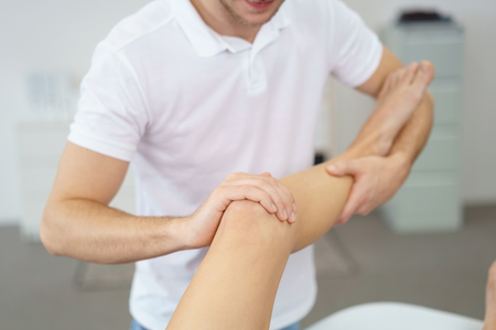 manipulating: Close up Professional Male Physical Therapist Helping his Patient in Exercising the Injured Leg.