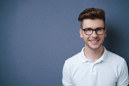 anteojos: Sonriente joven atractiva agradable con un peinado de moda moderna que presenta contra un fondo gris oscuro con copyspace, la cabeza y los hombros retrato