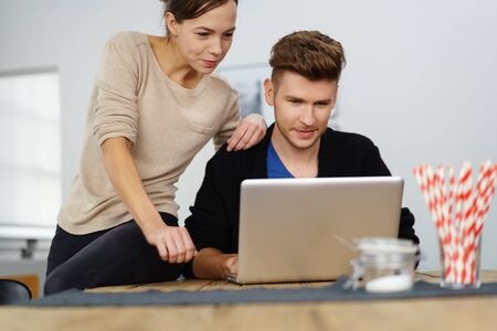 woman searching: man and woman couple in their twenties working on a laptop and looking at paperwork