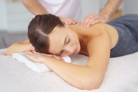 nudos: Cierre para arriba atractivo de la mujer joven que tiene un masaje de espalda Mientras yacía boca abajo en la cama en el Spa.