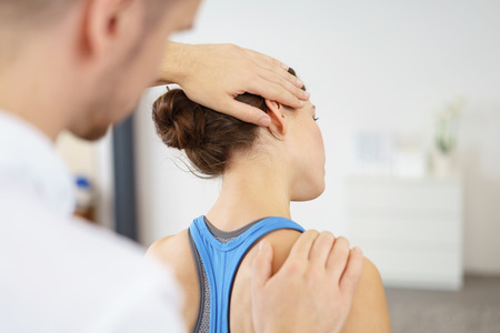 despacio: Close up Hombre Fisioterapeuta Estirar el cuello dañados de una paciente lentamente.