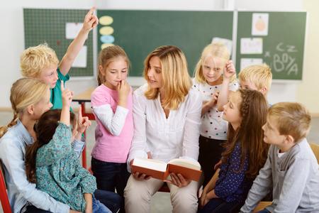 personas leyendo: Profesor Mujer enseñando algo a sus estudiantes de kindergarten de la historia en el libro dentro del aula.