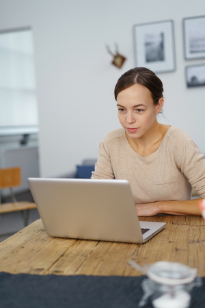 reviewer: Serious Young Woman Working on her Laptop Computer at the Table Inside the Office. Stock Photo
