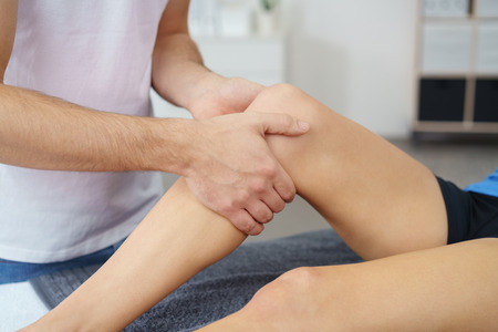 correctional: Close up Physical Therapist Massaging the Injured Leg of a Woman in the Clinic. Stock Photo
