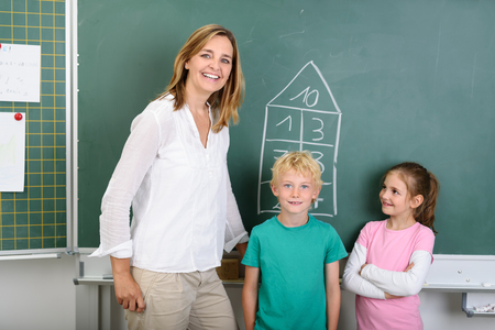 preteen boys: Happy Female Teacher with Two Kids Smiling at the Camera While Standing Against Green Chalkboard Inside the Classroom.