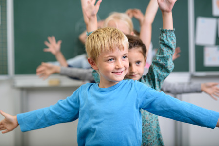 stretching: Half Body Shot of a Cute Boy Doing an Stretching Exercise inside the Classroom. Stock Photo