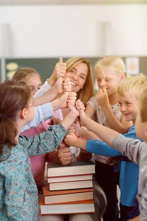 preschool children: Female Teacher and Kids Piling their Hands on Top of Books Together inside the Classroom, Showing Happy Facial Expressions. Stock Photo