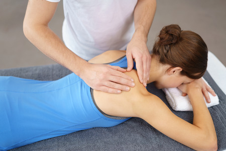 male massage: Physical Therapist Massaging the Back and Shoulder of a Female Patient, Lying Prone on the Bed.