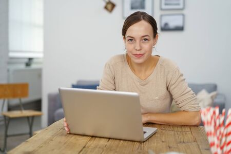 looking to camera: Young Woman, Sitting at her Wooden Office Desk with Laptop Computer, Looking at the Camera with Half Smile Face.