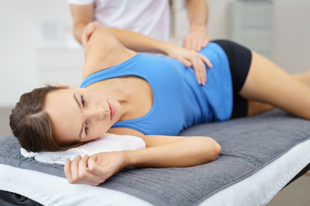 física: Mujer joven que miente en su lado en la cama mientras el terapeuta físico está dando un tratamiento a su cuerpo herido.