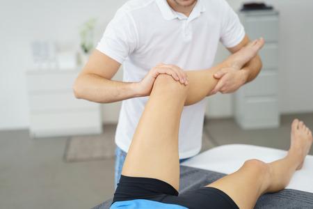in tears: Profesional Fisioterapeuta El levantamiento de la pierna dañada de un paciente y masajeando lentamente.