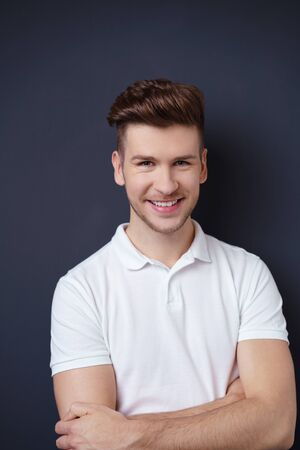 smiling man with trendy hairstyle standing against dark background with arms crossed