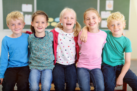 niños riendose: Cinco Kindergarten mejores amigos que se detienen por los hombros dentro de su aula con las expresiones faciales feliz.