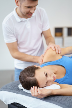 lying on side: Young Male Osteopath Massaging the Injured Shoulder of his Female Patient Inside the Clinic.