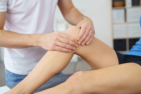 Professionale Fisioterapista Massaggiare il ginocchio infortunato di un paziente in clinica.
