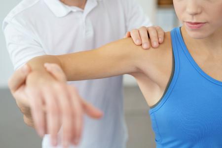 Close-up Professional Fysiotherapeut Het opheffen van de arm van zijn vrouw geduldig terwijl onderzoeken van de geblesseerde schouder.