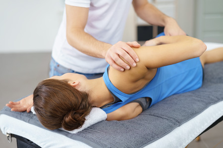 Male Osteopath Stretching the Injured Body of his Female Patient Lying on a Therapy Bed. Stock Photo