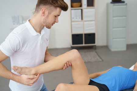 orthopaedic: Young Professional Male Physical Therapist Examining the Injured Knee of a Female Patient Inside the Clinic.