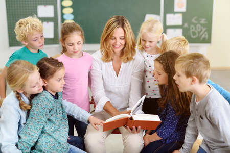 Female Teacher Reading a Story From the Book to her Little Young Students Inside the Classroom Stock Photo