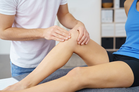 manipulating: Male Physical Therapist Checking the Knee Condition of a Female Patient Sitting on the Bed. Stock Photo
