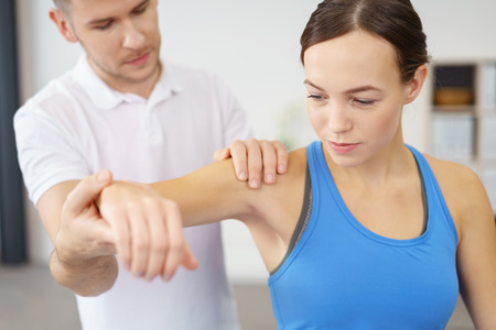 injured person: Professional Male Physical Therapist Helping his Female Patient in Exercising the Injured Shoulder. Stock Photo