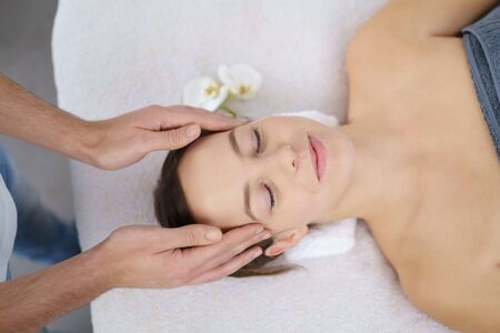 energising: High Angle View of a Young Woman Lying on Bed and Enjoying a Head Massage in the beauty center
