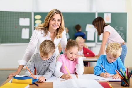 Довольно Учитель улыбается на камеру, помогая детей, отвечая на их экзамены внутри класса. Фото со стока
