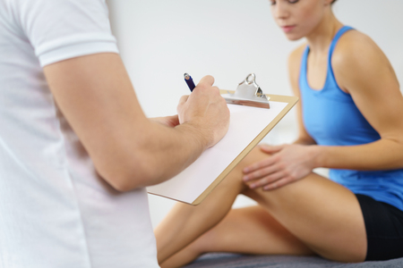 Physical Therapist Recording the Knee Condition of a Female Patient on a Paper Inside the Clinic.